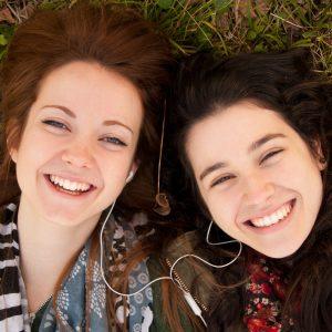 Two happy teenage girls lying on the grass sharing earphones