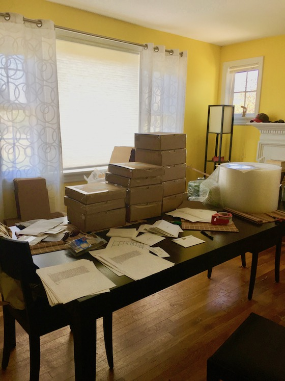 a large dining room table covered in cardboard boxes, mailing lablels, and bubble wrap
