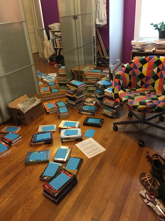 small stacks of books all over Rebecca's hardwood floor