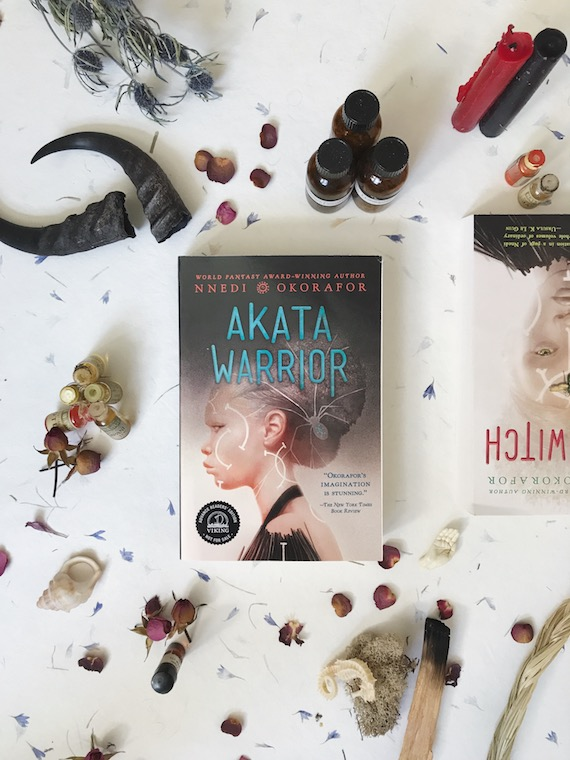 image of Akata Warrior and Akata Witch by Nnedi Okorafor layed out on top of paper surrounded by flowers, essential oils, candles, and other natural props