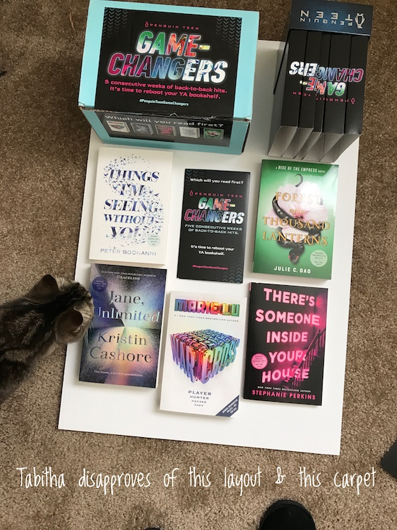 "image of six books layed out on white paper and a cat inspecting them with text, ""Tabitha disapproves of this layout & this carpet"""