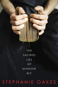 The Sacred Lies of Minnow Bly cover design: girl in all black zoomed in holding a book