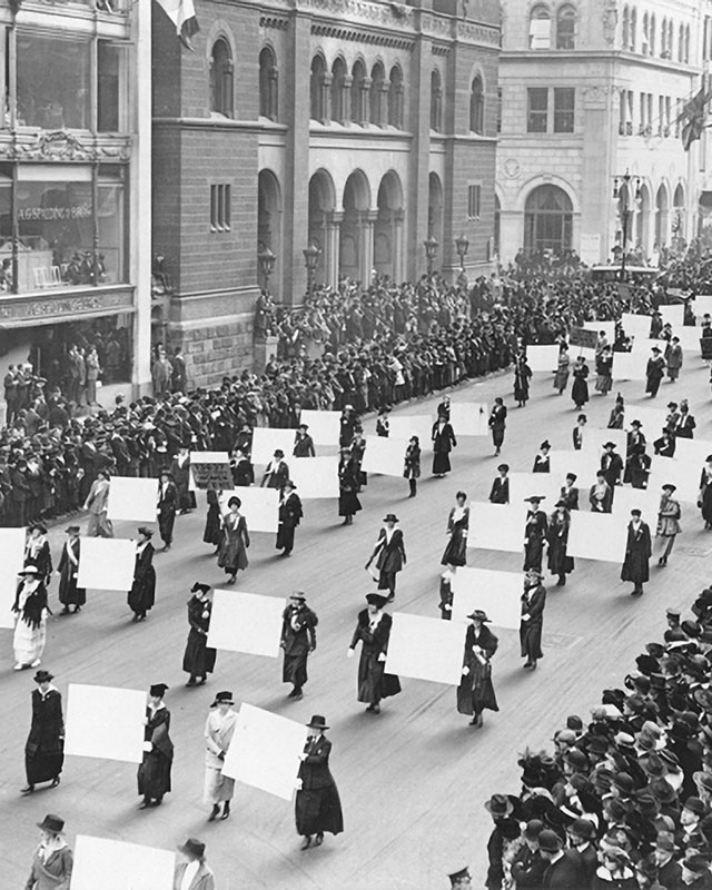 a black and white photo of US suffragists marching down a wide city street, carrying banners
