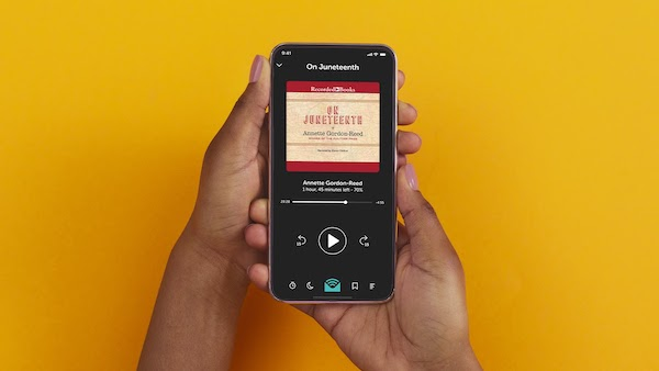 hands holding a mobile phone displaying the audiobook cover image of On Juneteenth by Annette Gordon-Reed