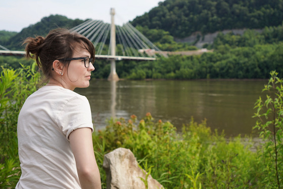 A photo of Kendra, a 30-something white woman with brunette hair, staring out across the Ohio River. There is a bridge in the background.