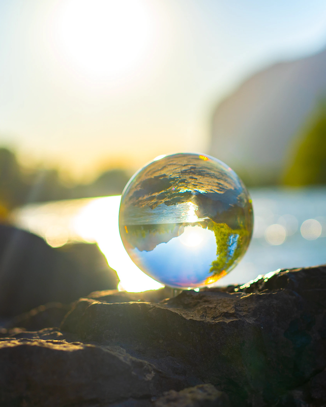 a photo of a clear marble balanced on a rock in fron of a lake, reflecting the rocks and water