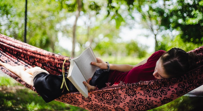 Image of a teen reading in a hammock.